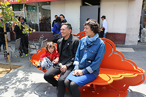 Arcega sits on a cloud bench with his daughter and wife