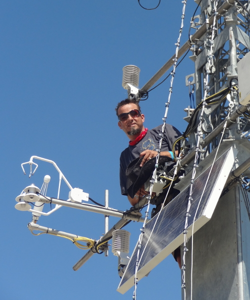 Man in sunglasses surrounded by scientific equipment peers down at the camera
