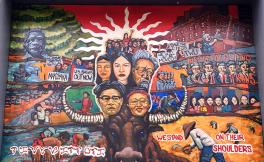 A colorful mural with a brown buffalo, and depictions of the faces of Asian American historical figures. Images of the 1968 Third World Liberation Front strikers are also present.