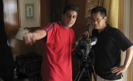 Arthur Dong stands behind a video camera and to the right of Allan Barrett