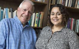 Professors Joel Kassiola and Marcela Garcia-Castañon are smiling with book-lined shelves in the background.