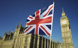 A photo of Great Britain's Parliament with a British flag waving in the foreground