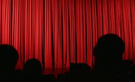 Photo of a theatre stage with a red curtain and silhouettes of people facing the stage