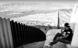 Deported U.S. Army military veteran Jose Francisco Lopez Moreno overlooks the fence separating him from the United States.