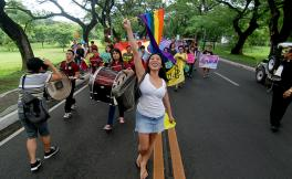 Photo in Philippines of activist Santy Layno leading a procession and waving the pride flag