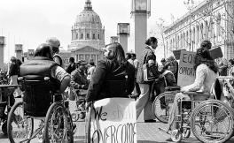 Black and white photo of protesters in wheelchairs by San Francisco City Hall with one holding sign with text We Shall Overcome