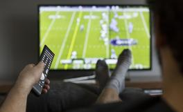 A photo of a man sitting on a couch watching football on TV.