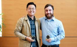 Two students stand side-by-side holding their awards