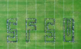Students form the letters SFSU on a green field