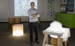 Artist Nathan Byrne stands next to his artwork