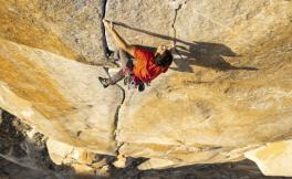 Man in red shirt climbing a granite wall far off the ground