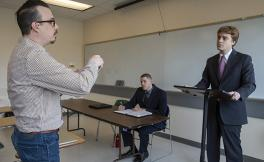 Moot Court Club president stands behind a podium in a classroom as SF State Political Science Assistant Professor Nick Conway and Aaron Gamez watches as he sits at a nearby table