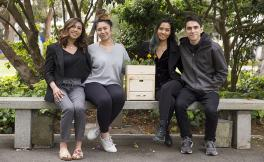 Three female students and one male student posing with their compost machine.