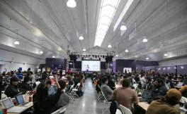 Students seated at long tables look towards a speaker on a stage in the distance.
