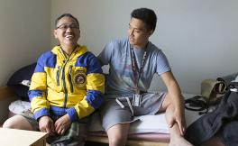 A student and family member sit on a bed inside a dorm room