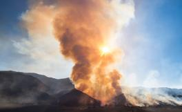 Reddish brown smoke rises from hills during the daytime