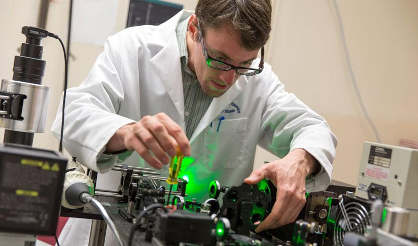 A photo of SF State student Alex Yore working in a physics lab.