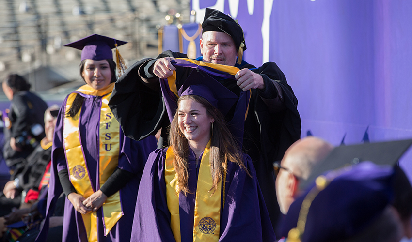 The dean bestows graduate Talia Hart with a hood during Commencement