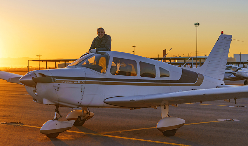 Jason poses by his airplane at an airport as the sun sets in the background.