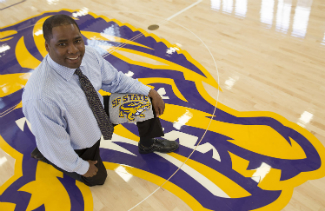 SF State's director of athletics, Charles Guthrie, in the newly renovated gymnasium with the updated Gator mascot.