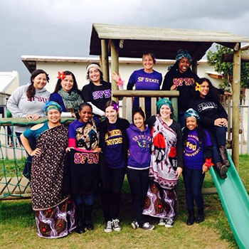 Lygia Stebbing, professor of child and adolescent development at SF State, and a group of 11 SF State students and recent graduates that volunteered in South African preschools pose at a playground.