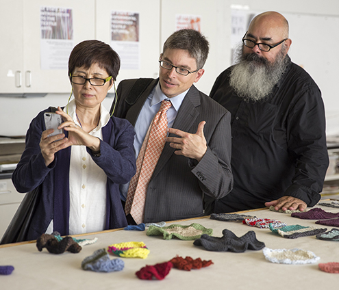 Visiting Chinese fiber artist Shi Hui (left) photographs student artwork presented by Victor De La Rosa, associate professor of art (right). Frederik Green (center), associate professor of Chinese, translates.