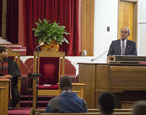 President Les Wong stands behind a podium and looks out at the congregation at Providence Baptist Church.