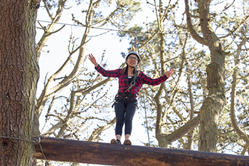 Student Kathy Vu balances on a utility pole at SF State's ropes course.