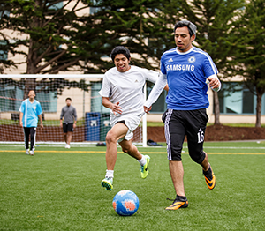 Two students chase a soccer ball on the field in front of student housing units, as two other players look on.