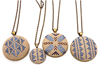 Four cross-stitched necklaces made by