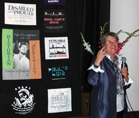 Photo of Catherine Kudlick with a microphone, standing next to a quilt made out of the late Paul Longmore's collection of disability related T-shirts.