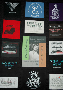 Photo of a quilt with a black background and 20 images taken from Paul Longmore's collection if disability related T-shirts.