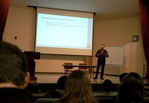 Photo of students and members of the public in a lecture hall, with Michael Bar lecturing from the stage.