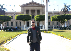 Photo of Associate Professor of International Relations Mahmood Monshipouri in front of a Cairo University building.