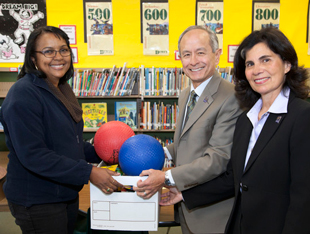 Photo of President Les Wong and Phyllis Wong giving a box of school supplies and basketballs to JoLynn Washington, principal at Jose Ortega Elementary School.
