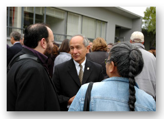 Photo of University President Les Wong talking with faculty at a reception