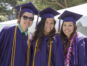 A photo of three graduating students during Commencement at SF State.