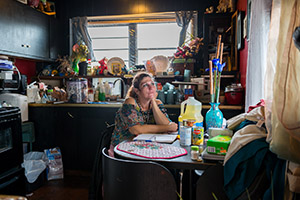 A photo of a woman, photographed as part of The Debt Project, sitting at a kitchen table