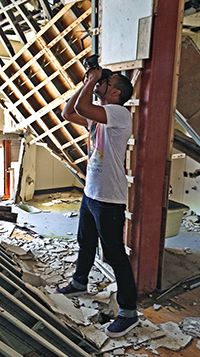 A photo of SF State student Gavin McIntyre taking photos in a destroyed middle school gymnasium.