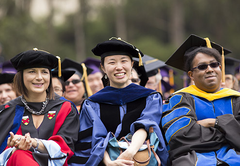 Three members of the audience during SF State's graduate Commencement ceremony