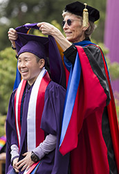 A photo of a student receiving a graduate hood.