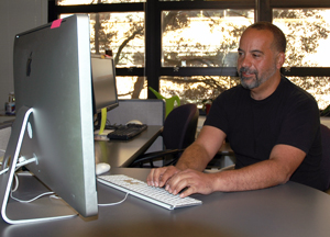 A photo of Web Specialist Julio Feliciano working at a computer.