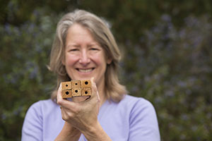 Professor of Biology Gretchen LeBuhn holds examples of bee nesting sites