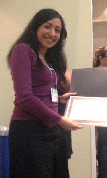 A photo of graduate student Shad Kish holding her award at the CSU Research Competition.