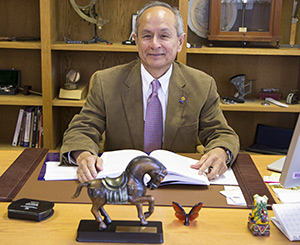 A photo of SF State President Leslie Wong at his desk with the APAHE President's Award.