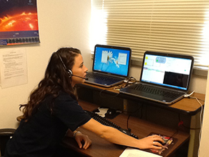 Laura King sits in front of two computer consoles during a time-delay simulation.