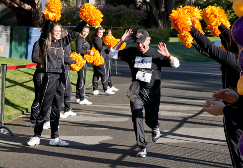 A photo of President Leslie E. Wong crossing the finish line during the XLR8@SF State 5K Walk/Run.