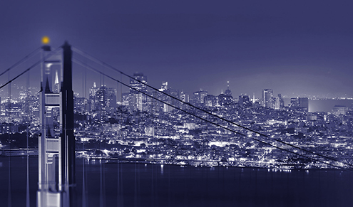Image of San Francisco at night with the Golden Gate Bridge in the foreground.