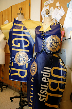 A photo of two dresses made from old SF State banners hanging in a classroom.