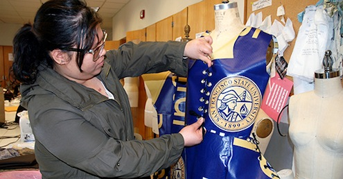 A photo of SF State student Helen Nguyen adjusting a dress she designed from old SF State banners.